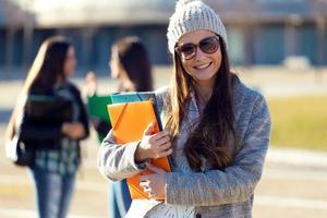 Studentin, die Kamera im Campus der Universität betrachtet. foto