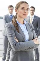 Porträt der selbstbewussten Geschäftsfrau, die Arme mit Kollegen verschränkt foto