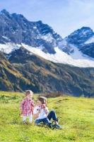 glückliche drei Kinder, die zusammen neben schneebedeckten Bergen spielen foto