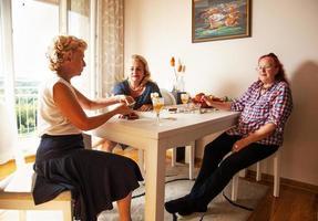 ältere Frauen, die im Wohnzimmer plaudern und Karten spielen foto