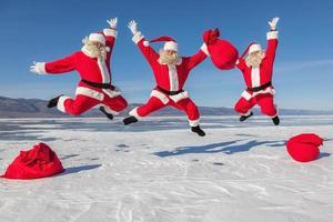 drei springende Weihnachtsmänner im Freien