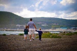 Vater geht mit seinen Kindern am Strand entlang foto