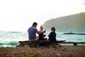 Vater sitzt mit seinen Kindern am Strand foto