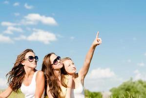 Drei glückliche Teenager-Mädchen tauchen im Copyspace des blauen Himmels auf foto