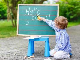 niedlicher kleiner Junge mit Brille an der Tafel, die das Schreiben übt foto