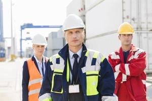 selbstbewusste Arbeiter, die in der Schifffahrtswerft stehen foto