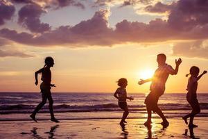 Vater und Kinder spielen am Strand