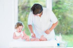 Neugeborenes Baby betrachtet seinen Vater und seine Schwester, die Windel wechseln foto