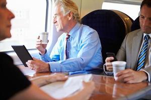 Geschäftsmann, der im Zug mit Tasse Kaffee entspannt foto