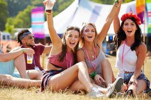 Freunde sitzen auf dem Rasen und jubeln einem Musikfestival zu foto