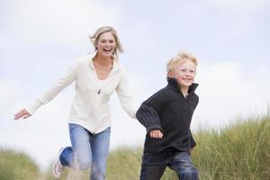 Mutter und Sohn laufen am Strand lächelnd foto