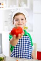 kleiner niedlicher Kinderjunge mit Kochhut, der Tomate hält