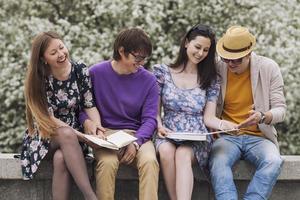 vier Freunde im Park mit Büchern foto