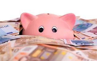 einzigartiges rosa keramisches Sparschwein, das im Geld ertrinkt foto