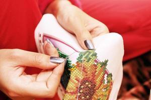Stickprozess auf Stoffperlen Hände
