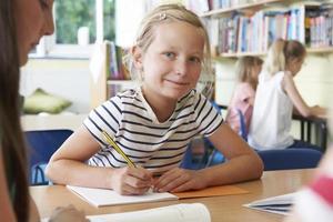 Grundschüler, der am Schreibtisch im Klassenzimmer arbeitet foto