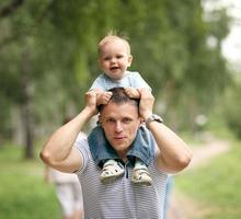 kleiner Junge, der mit Papa im Park spielt