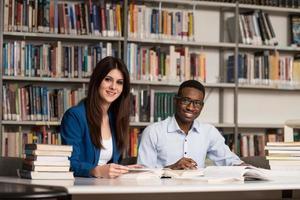 Gruppe junger Studenten, die in der Bibliothek sitzen foto
