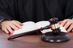 Richter liest Gesetzbuch am Schreibtisch foto