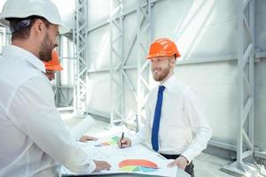 Erfolgreiche junge Architekten diskutieren den Projektplan foto