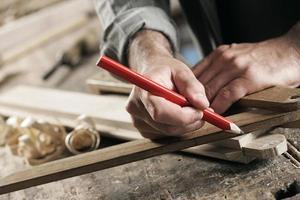 Nahaufnahme des Zimmermanns, der ein Holzbrett markiert foto