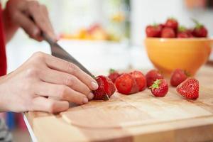 Nahaufnahme der Frau, die Obstsalat vorbereitet foto