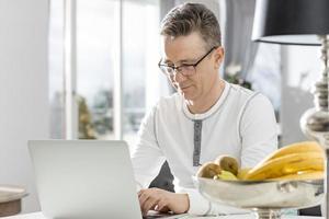 reifer Mann mit Laptop am Tisch im Haus foto