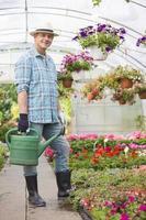 Porträt des lächelnden Mannes, der Bewässerungsdose im Gewächshaus trägt