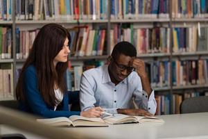 männlicher Student, der in der Bibliothek schläft foto
