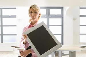 Geschäftsfrau, die Computermonitor im leeren Büro hält foto