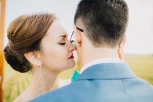 Bräutigam küsst Braut im Feld foto