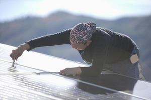 Ingenieur repariert Solarpanel auf dem Dach foto