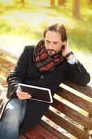 Mann mittleren Alters, der draußen auf der Bank ruht foto