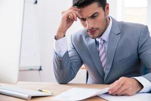 schöner Geschäftsmann, der am Tisch im Büro sitzt foto