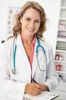 Ärztin mittleren Alters, die ein Rezept schreibt