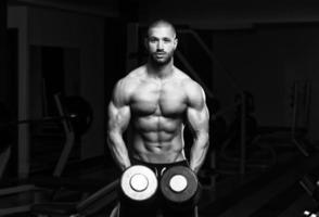 Bodybuilder trainieren Schultern mit Hanteln