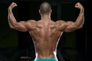 körperlich Mann zeigt seinen gut trainierten Rücken foto