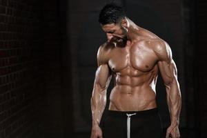 Mann mit Ketten zeigt seinen gut trainierten Körper foto