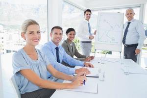 Geschäftsteam während des Treffens lächelnd in die Kamera
