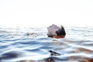 in den Problemen versinken. junger Mann, der Schmerz und Enttäuschung erfährt foto