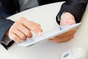 Geschäftsmannfinger, der auf den Bildschirm eines digitalen Tablets zeigt.