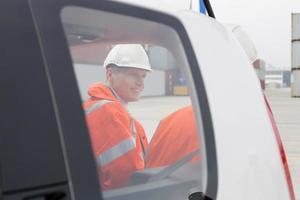 Ingenieure unterhalten sich neben dem Auto in der Werft foto