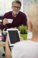 Mann trinkt Kaffee und hört seiner Sekretärin zu foto