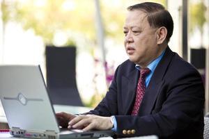 asiatischer Geschäftsmann mit Laptop-PC