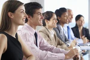 Linie von Geschäftsleuten, die Präsentation hören, die an Glas sitzt foto