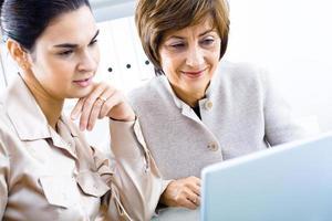 zwei Geschäftsfrau, die blauen Laptop während bei der Arbeit betrachtet foto