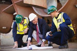 Arbeiter lesen Blaupausen auf Trockendock