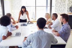 Geschäftsfrau, die Kollegen bei einem Treffen vorstellt foto