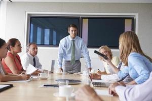 Gruppe von Geschäftsleuten, die sich um den Sitzungssaaltisch treffen