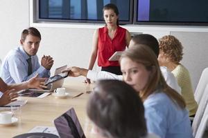 Gruppe von Geschäftsleuten, die sich um den Sitzungssaaltisch treffen foto